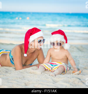 Baby and mother on the beach. Christmas concept - Stockfoto