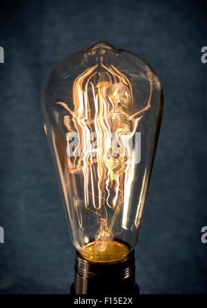 Horrifying vintage Halloween themed skeleton trapped inside lightbulb - Stock Photo