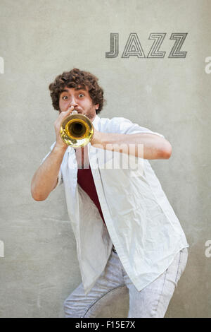 curly haired man plays jazz trumpet outside stock photo