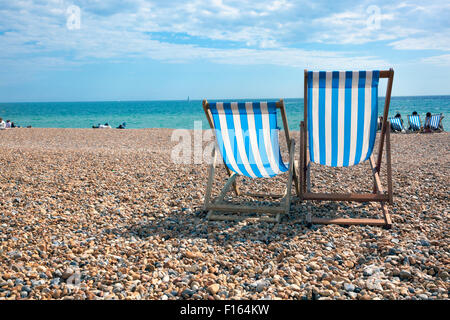 Two deck chairs on the beach facing sea, Brighton, UK - Stock Photo