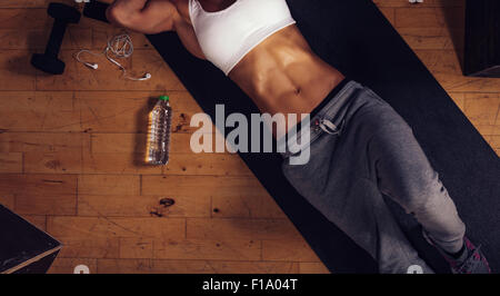 Top view of young woman with muscular abs lying on yoga mat in gym. Cropped shot of fitness woman relaxing after - Stock Photo