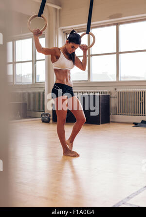 Full length shot of fit young woman resting after exercising on gymnastic rings. Female in sports wear standing - Stock Photo
