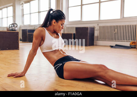 Portrait of muscular young woman relaxing after workout at gym. Fit female athlete taking a break from workout. - Stock Photo