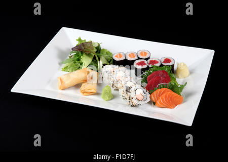 menu of sushi and sashimi with wasabi and vegetable in white plate on a black background - Stock Photo