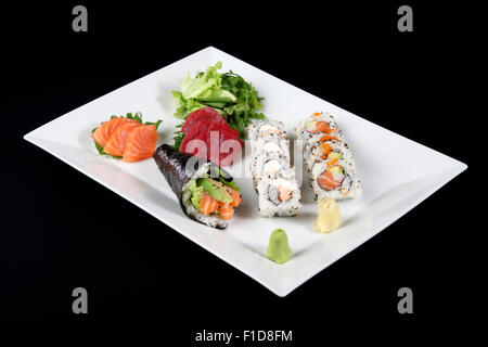 sushi and sashimi with wasabi and vegetable in white plate on a black background - Stock Photo