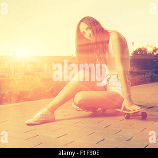 Color toned image og young girl sitting on her skateboard - Stock Photo