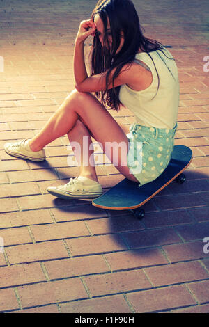 Sporty girl sitting on her skateboard and looking back at camera - Stock Photo