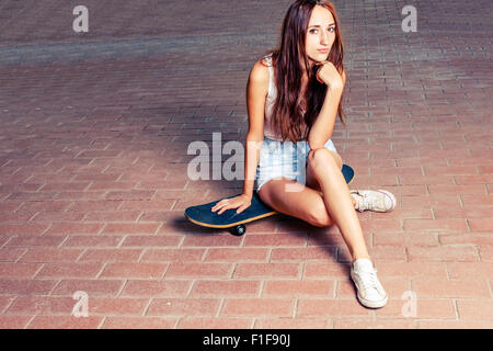 Redhair women is sitting on skateboard outdoors - Stock Photo