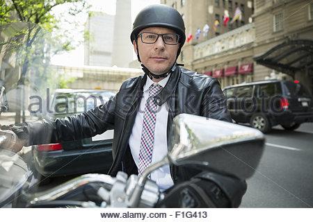 Portrait confident businessman commuting on motorcycle - Stock Photo