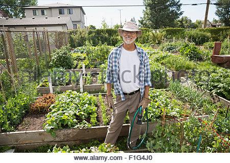 Portrait smiling man in vegetable garden - Stock Photo