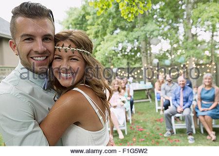 Portrait enthusiastic bride and groom at backyard wedding - Stock Photo
