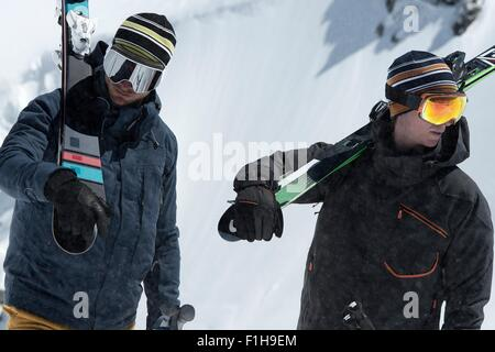 Two men carrying skis in snow - Stock Photo