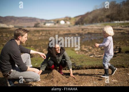 Mother and father playing with son, making pile of soil - Stock Photo