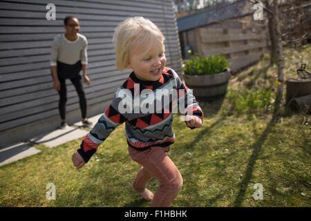 Boy running in garden, smiling - Stock Photo