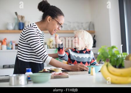 Son feeding mother food in kitchen - Stock Photo
