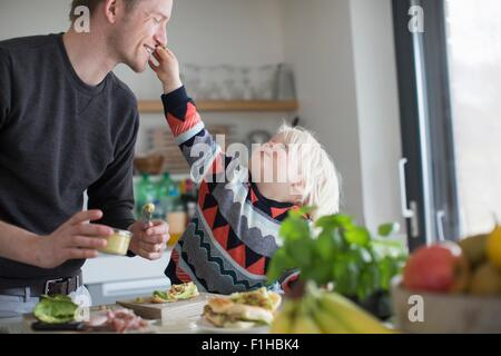 Boy touching father's face in kitchen - Stock Photo