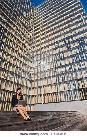 Businesswoman using laptop in front of high rise building, Paris, Île-de-France, France - Stock Photo