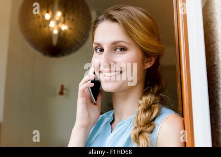 Portrait of young woman chatting on smartphone in cafe doorway - Stock Photo