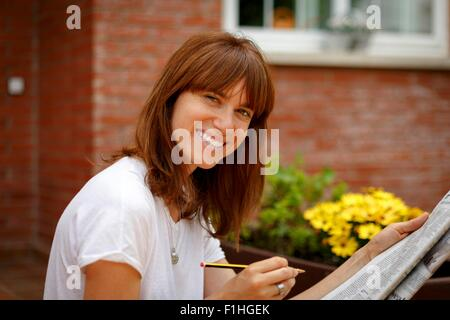 Mid adult woman sitting outdoors doing crossword, looking at camera, smiling - Stockfoto