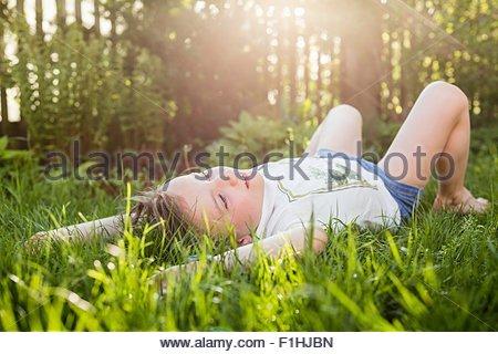 Girl lying on grass gazing in garden - Stock Photo
