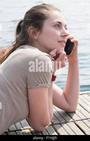 Young woman lying on pier chatting on smartphone, Lake Mergozzo, Verbania, Piemonte, Italy - Stock Photo