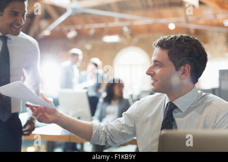 Businessmen with paperwork in office - Stock Photo