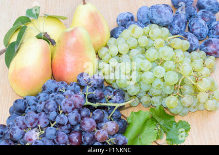 Grape, pears and plums on a wooden table - Stockfoto