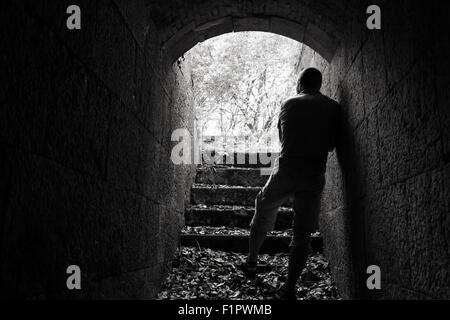 Young man stands in dark stone tunnel with glowing end, black and white photo - Stock Photo