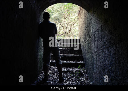 Young man stands in dark stone tunnel with glowing end, vintage tonal correction filter effect - Stock Photo