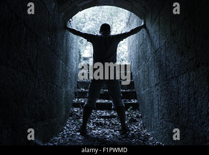 Young man stands in dark stone tunnel with glowing end, blue tonal correction filter - Stock Photo