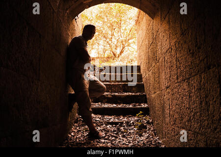 Young man stands in dark stone tunnel with glowing end, warm tonal correction filter - Stock Photo