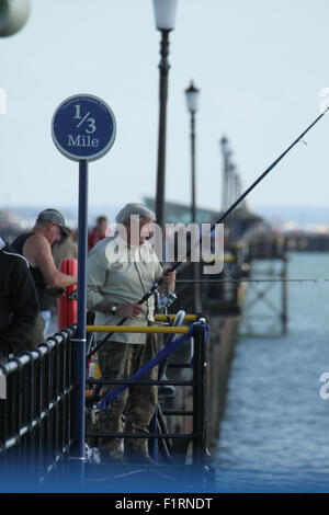 Southend On Sea, UK 6 September 2015. A group of friends seen setting up their fishing hooks on the Southend pier. - Stockfoto