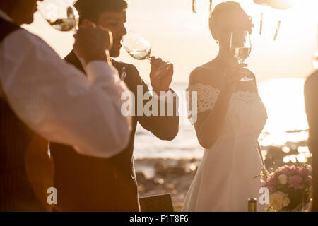 Drinking champagne at wedding reception on the beach - Stock Photo