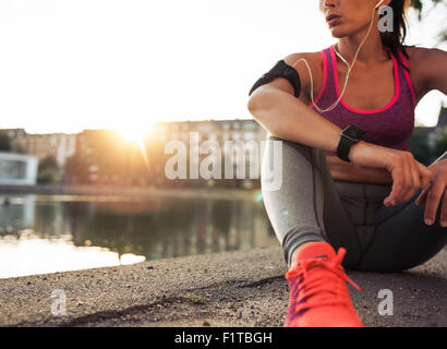 Young woman runner resting after workout session on sunny morning. Female fitness model sitting on street along - Stock Photo