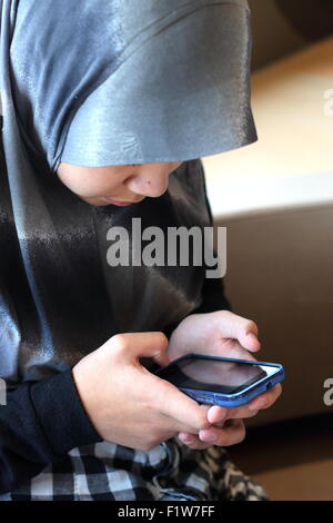 Muslim girl in Hijab with mobile phone - Stock Photo