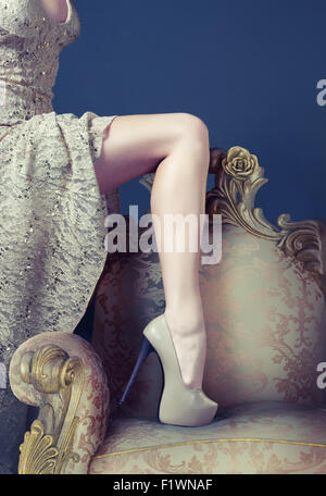 Beautiful slim leg on the luxury vintage armchair - Stock Photo