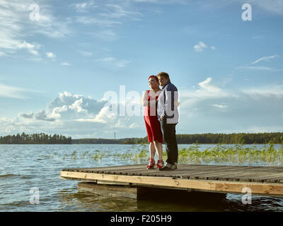 Lovely couple standing on the boat dock, warm summer evening light - Stock Photo
