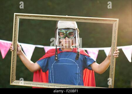 Portrait of boy looking through picture frame wearing cape, goggles and flying hat - Stock Photo