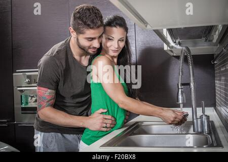 Young woman washing up whilst being embraced by boyfriend - Stock Photo