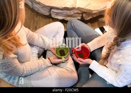 High angle view of two young women drinking herbal tea in front of fireplace - Stockfoto