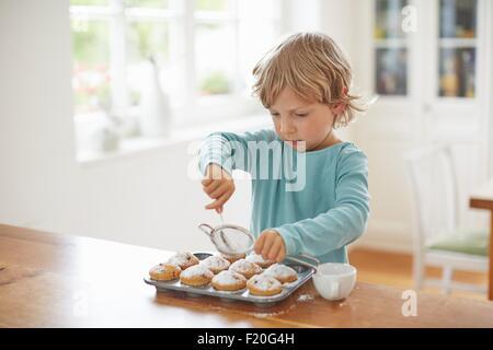 Boy making cupcakes in kitchen - Stock Photo