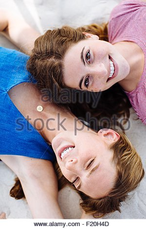 Overhead portrait of two young female friends lying on beach - Stock Photo