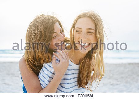 Two young female friends laughing on beach - Stock Photo