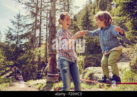 Boy balancing on rope with help from mother, Ehrwald, Tyrol, Austria - Stock Photo