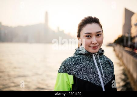 Portrait of young woman wearing tracksuit top in front of water smiling - Stock Photo