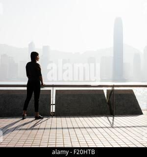 Silhouetted side view of young woman standing looking out over water at skyline, Hong Kong, China - Stock Photo