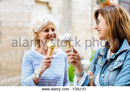 Two mature female friends eating ice cream cones, Tuscany, Italy - Stock Photo
