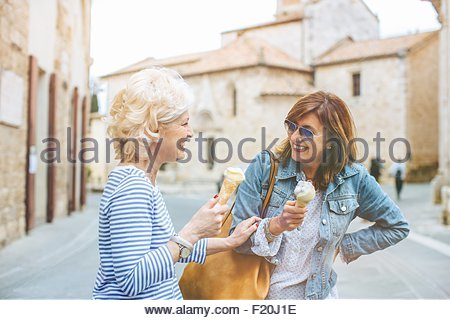 Two mature female friends eating ice cream cones and laughing, Tuscany, Italy - Stock Photo