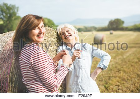 Two mature female friends with straw grass, Tuscany, Italy - Stock Photo