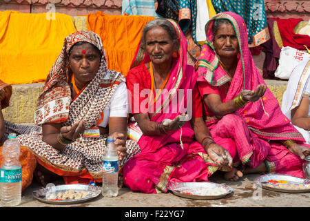 Pilgrims hold out palms as they wait to receive prasad (food as a religious offering) on the ghats beside the Ganges - Stock Photo